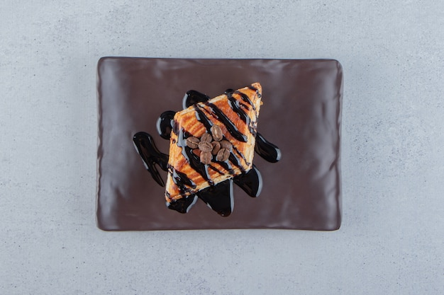 Pâtisserie sucrée décorée de chocolat placé sur une assiette noire