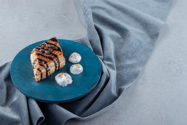 Pâtisserie sucrée décorée de chocolat placée sur une planche bleue