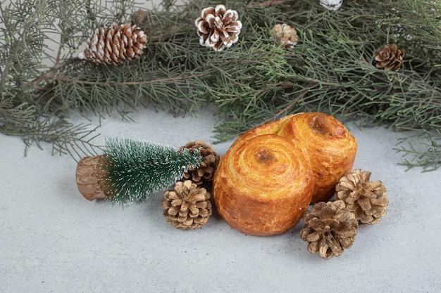 Pâtisserie sucrée avec des pommes de pin de noël sur une surface blanche