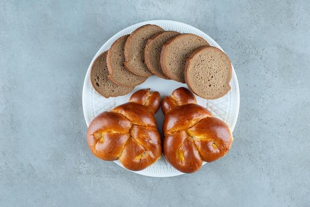 Pâtisserie sucrée et tranches de pain sur plaque blanche.