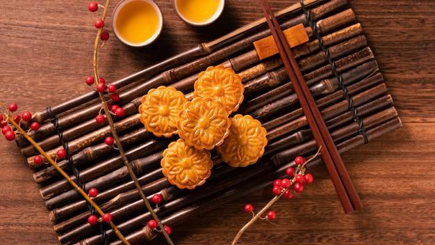 Pâtisserie traditionnelle chinoise mooncake mooncake avec des tasses à thé sur un plateau de service en bambou sur fond de bois pour la fête de la mi-automne, vue de dessus, mise à plat