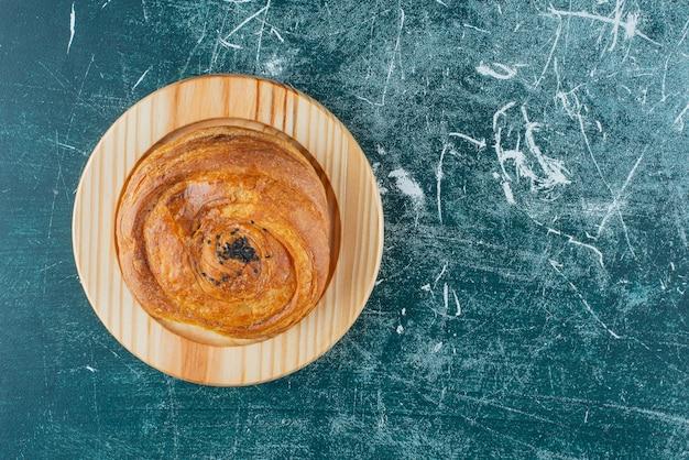 Pâtisserie traditionnelle décorée de graines de sésame sur plaque de bois.