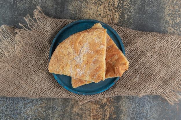 Pâtisserie triangulaire avec du sucre sur une plaque bleue