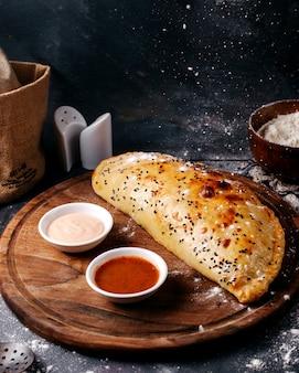 Pâtisserie vue de face avec des sauces blanches et rouges sur le bureau rond en bois marron et surface grise