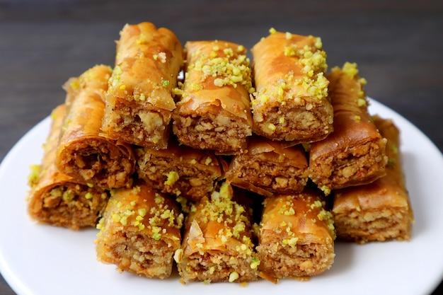 Pâtisseries baklava garnie de pistaches hachées sur tableau noir