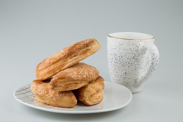 Pâtisseries dans une assiette avec une tasse en surface blanche