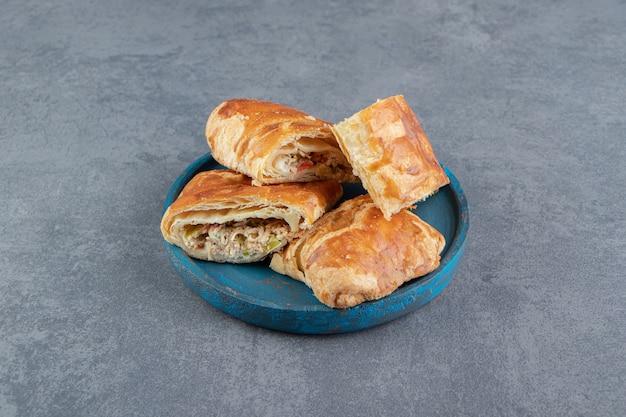 Pâtisseries farcies de forme carrée sur plaque bleue.