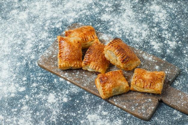 Pâtisseries avec farine saupoudrée sur béton et planche à découper