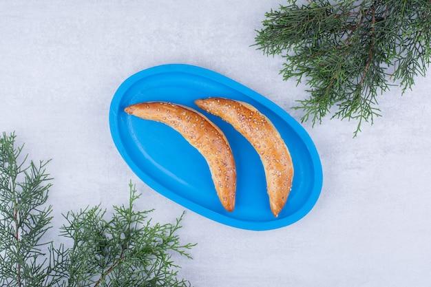 Pâtisseries en forme de lune sur plaque bleue avec branche de pin.