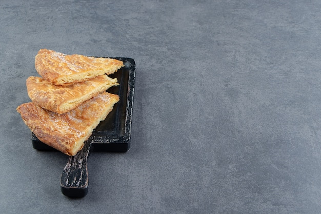 Pâtisseries en forme de triangle sur une planche à découper noire.