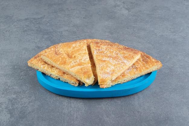 Pâtisseries en forme de triangle sur plaque bleue.