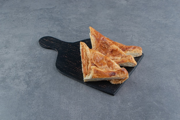 Pâtisseries en forme de triangle remplies de fromage sur planche de bois.