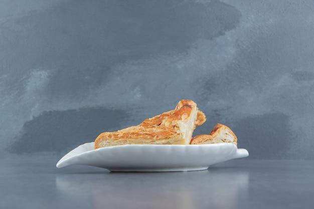 Pâtisseries en forme de triangle remplies de fromage sur une plaque blanche.
