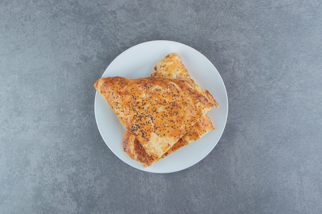 Pâtisseries en forme de triangle remplies de viande sur plaque blanche.