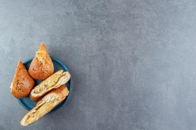 Pâtisseries fraîches aux graines de sésame sur plaque bleue.