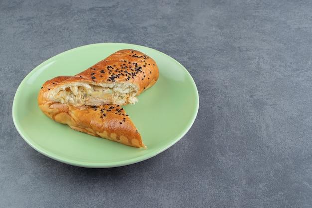 Pâtisseries fraîches aux graines de sésame sur plaque verte.