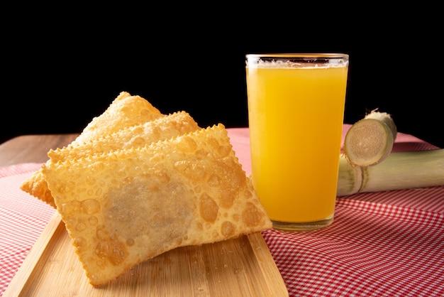 Pâtisseries frites brésiliennes, un verre de jus de canne à sucre et des cannes positionnées sur une nappe à carreaux