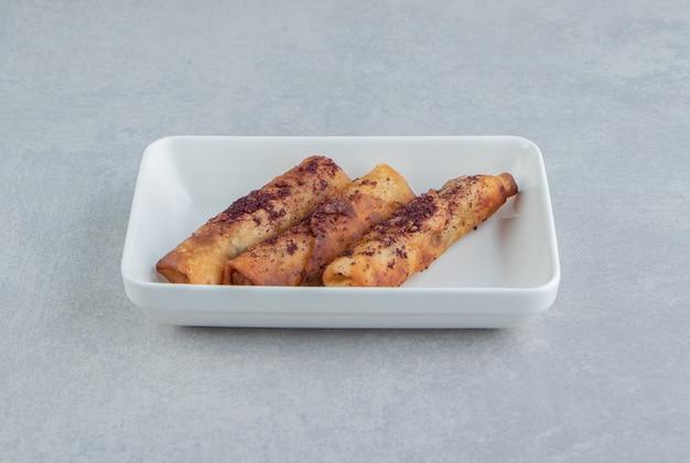 Pâtisseries frites en forme de cigare dans un bol blanc.