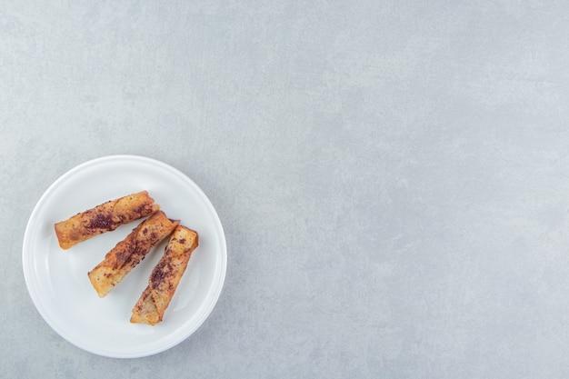 Pâtisseries frites en forme de cigare sur plaque blanche.
