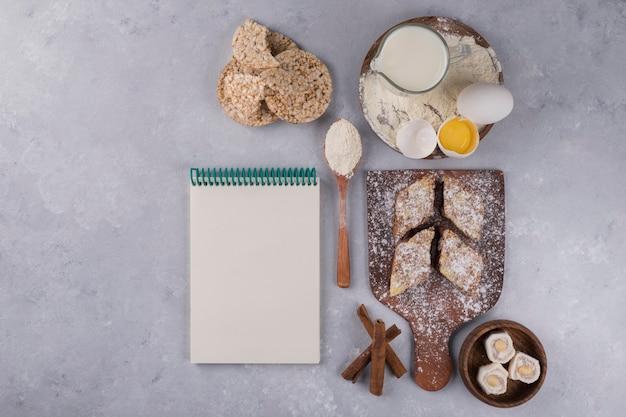 Pâtisseries, ingrédients et livre de recettes à côté