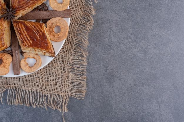 Pâtisseries maison et fruits secs sur plaque blanche.