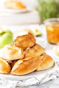 Pâtisseries russes traditionnelles remplies de pommes sur une plaque blanche