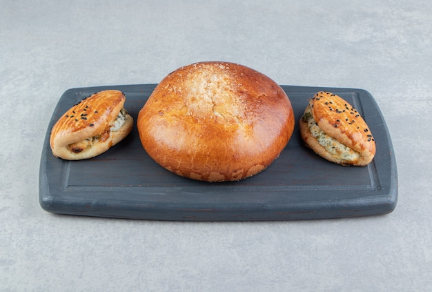 Pâtisseries savoureuses avec du fromage et du pain sur tableau noir.