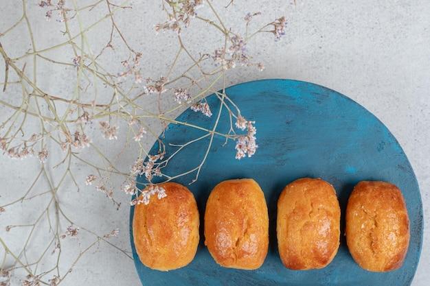 Pâtisseries sucrées avec fleur fanée en assiette bleue.