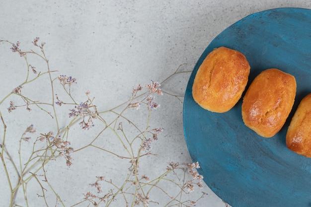 Pâtisseries sucrées à la fleur fanée en plaque bleue