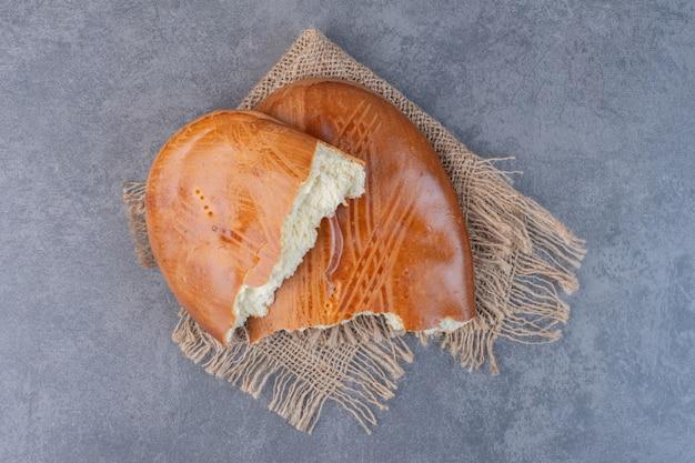 Pâtisseries sucrées maison demi-coupées sur toile de jute.