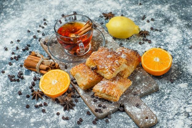 Pâtisseries avec thé, farine, chips de choco, épices, orange, citron sur béton et planche à découper