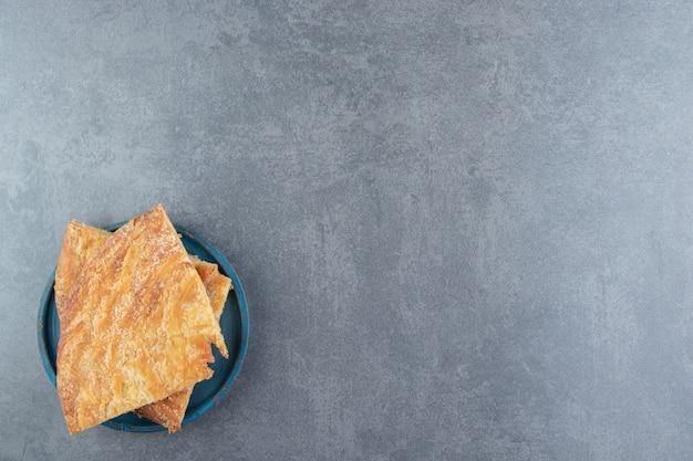 Pâtisseries triangle fraîches faites maison sur plaque bleue.