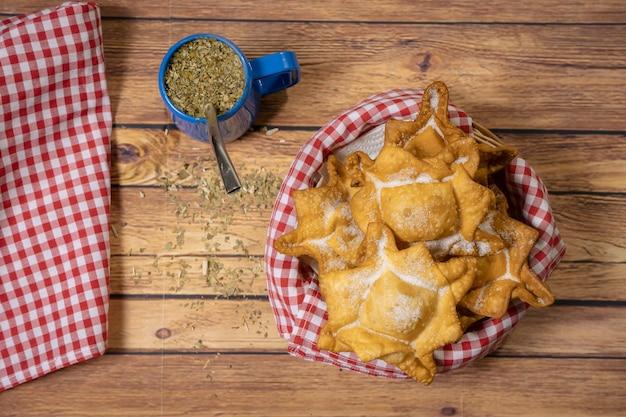 Pâtisseries typiques de patates douces et coings frites sur un plateau accompagnées du maté classique