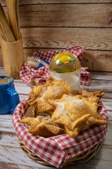 Pâtisseries typiques de patates douces et coings frits sur un plateau accompagnés du maté classique sur une vieille table en bois. concept de cuisine ethnique ou régionale. orientation verticale.