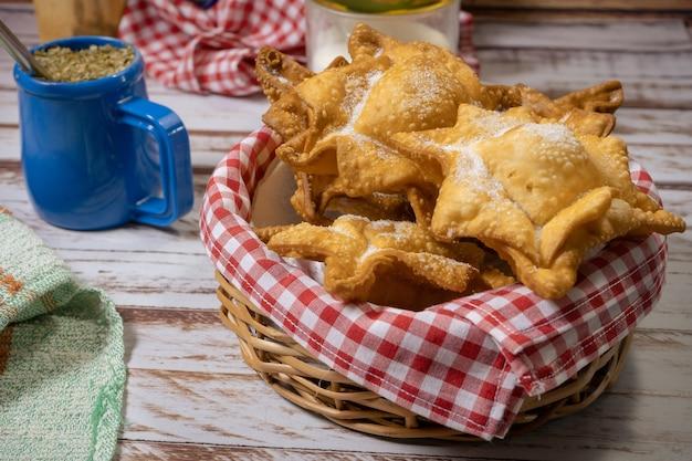 Pâtisseries typiques de patates douces et coings frits sur un plateau accompagnés du maté classique sur une vieille table en bois. concept de cuisine ethnique ou régionale. vue élevée