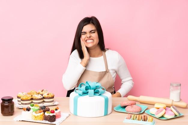 Pâtissier avec un gros gâteau dans une table sur un mur rose isolé avec mal de dents