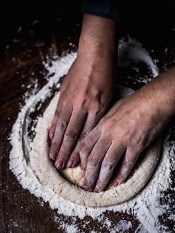 Pâtissier, main, pétrissage de la pâte crue avec de la farine blanche saupoudrée sur la table de la cuisine.