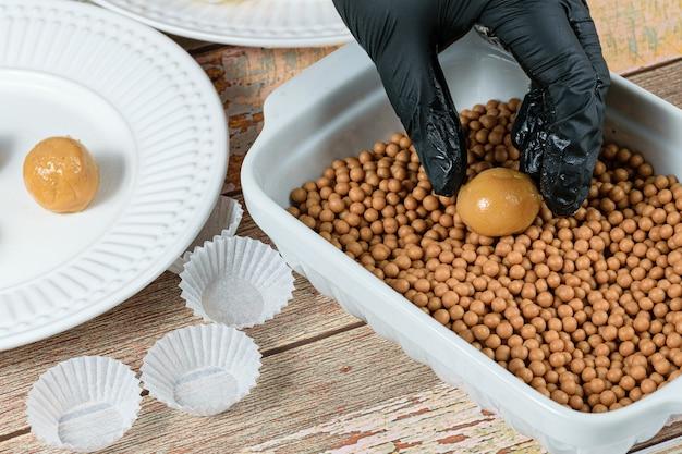 Pâtissier plaçant le brigadeiro (brigadier) de dulce de leche sur des caramels croquants salés.