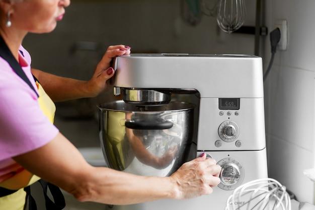 Pâtissier professionnel femme prépare un dessert. ajoute des ingrédients et mélange la pâte dans un mélangeur