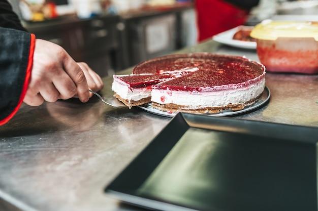 Pâtissier professionnel servant un délicieux gâteau.