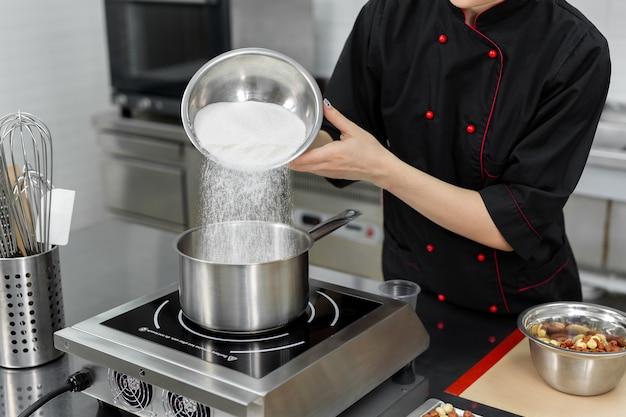 Le pâtissier verse le sucre dans une casserole.