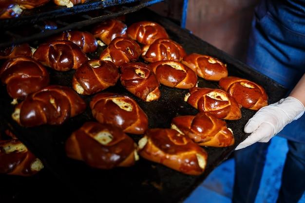 La pâtissière tient un plateau avec des pâtisseries chaudes dans la boulangerie. elle porte une robe en jean et une casquette. fabrication de produits de boulangerie. rack avec des pâtisseries fraîches croustillantes.