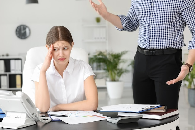 Patron en colère grondant sa secrétaire au bureau