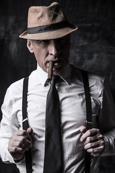 Patron confiant. homme senior autoritaire au chapeau fumant un cigare et ajustant ses bretelles en se tenant debout sur un fond sombre