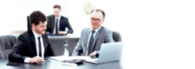 Patron et employé discutant du document assis au bureau du bureau. image floue pour le texte publicitaire. photo avec espace copie