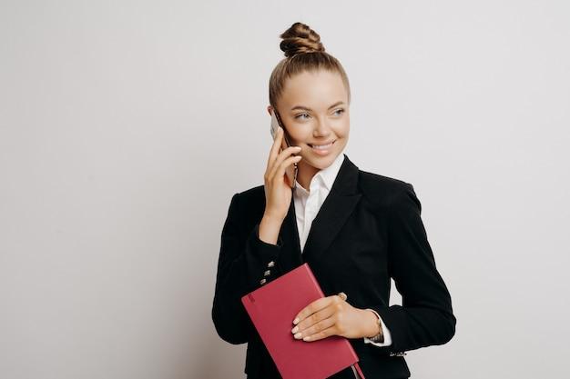 Patron féminin dans des vêtements classiques élégants regardant à droite avec un regard sitisfié parlant au téléphone et étant heureux d'entendre de bonnes nouvelles sur les résultats du travail, posant avec un ordinateur portable à la main isolé sur fond gris