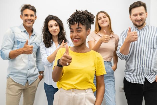 Patron de femme afro au bureau, collègues derrière