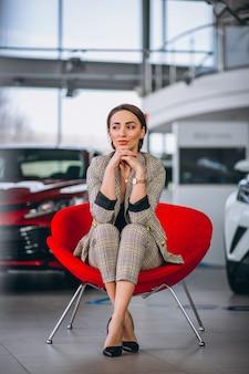 Patron femme, dans, a, voiture, showrrom, reposer, dans, a, chaise rouge