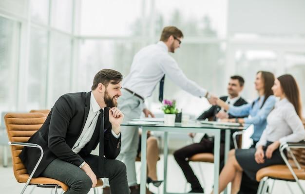 Patron sur le fond de la poignée de main d'un gestionnaire avec un client sur le lieu de travail dans un bureau moderne