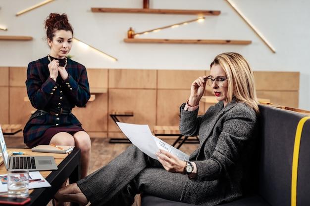 Patron à lunettes. patron aux cheveux blonds portant des lunettes lisant l'expérience de travail de l'employé